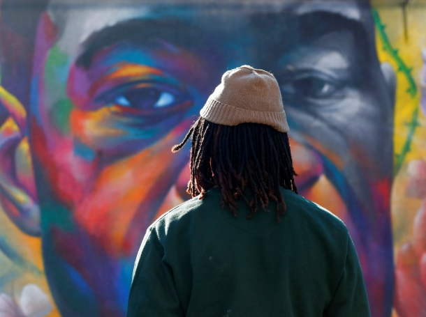 A person pays their respects at a mural of George Floyd after the verdict in the murder trial of former Minneapolis police officer Derek Chauvin, Denver, Colorado, April 20, 2021, photo by Kevin Mohatt/Reuters