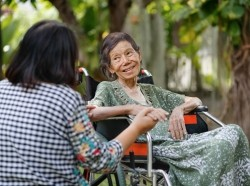Elderly Asian woman on wheelchair at home with daughter taking care of her, photo by Toa55/Getty Images