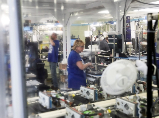 Employees assemble ventilator components behind a plastic curtain at a GE Healthcare manufacturing facility in Madison, Wisconsin, April 21, 2020
