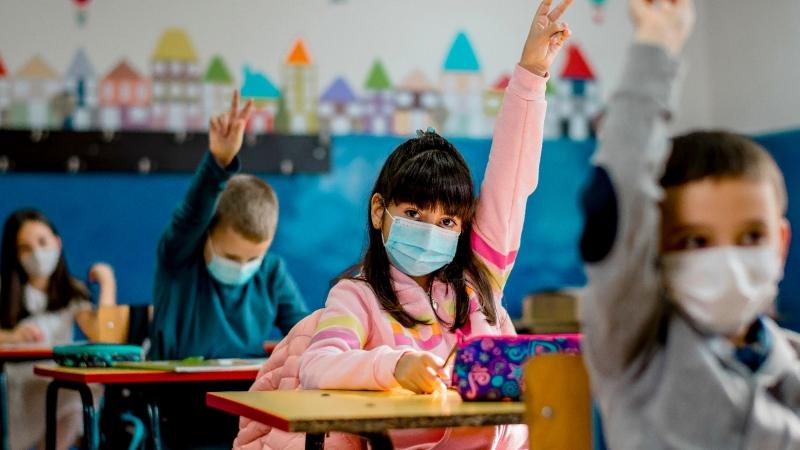 Elementary schoolchildren wearing face masks in a classroom, photo by kevajefimija/Getty Images