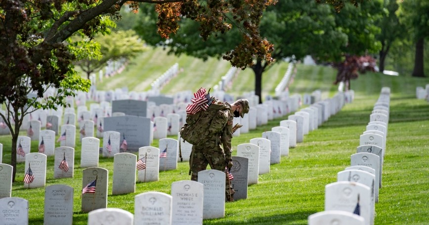 Soldiers assigned to the 3rd U.S. Infantry Regiment place American flags at headstones ahead of Memorial Day in Arlington National Cemetery, Arlington, Virginia, May 21, 2020, photo by Elizabeth Fraser/U.S. Army