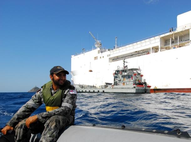 Royal Australian Navy Able Seaman Marine Technician Joey Mead operates a zodiac as the USNS <em>Mercy</em> transfers cargo aboard the HMAS <em>Labuan</em>, near Timor-Leste, August 15, 2010, photo by Mass Communication Specialist 2nd Class Eddie Harrison/U.S. Navy