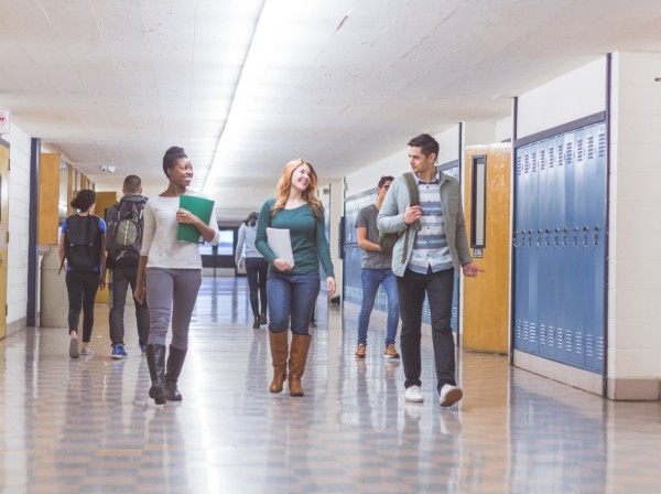 A group of students walk down the hallway in a high school, photo by FatCamera/Getty Images