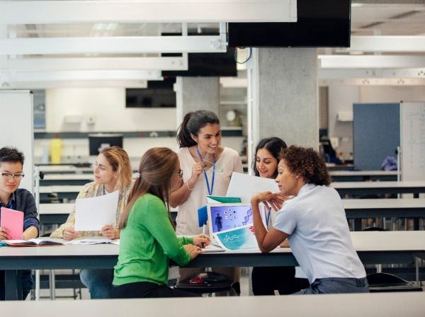 A laboratory classroom with a group of women science students working, photo by SolStock/Getty Images