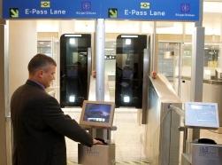 A man puts his biometric passport on a scanner at an automatic border control point at Zurich-Kloten airport near Zurich, Switzerland, December 1, 2010, photo by Arnd Wiegmann/Reuters