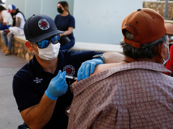 A health care worker from the El Paso Fire Department administers a COVID-19 vaccine at a vaccination center in El Paso, Texas, May 7, 2021, photo by Jose Luis Gonzalez/Reuters