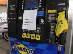 A driver walks to his car near an empty gas pump in Falls Church, Virginia, May 12, 2021, photo by Kevin Lamarque/Reuters