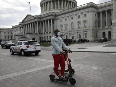 Two men ride electric scooters on Capitol Hill in Washington D.C., March 20, 2020, photo by Gripas Yuri/ABACA via Reuters