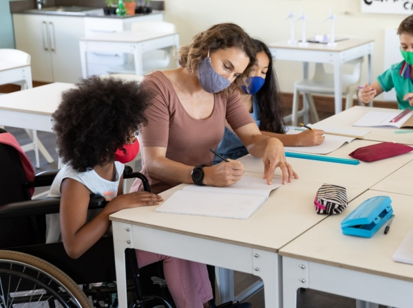 Teacher wearing a face mask works with students with disabilities in classroom, photo by Wavebreakmedia/Getty Images