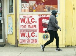 Woman walking by a convenience store with signs indicating acceptance of WIC and food stamps in Chelsea, Massachusetts, April 16, 2020, photo by Keiko Hiromi/Reuters