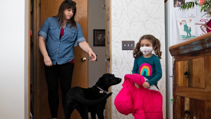 Food blogger Katy McAvoy reaches to hang up daughter Paige's jacket after her return from school in Grand Rapids, Michigan, March 2, 2021, photo by Emily Elconin/Reuters