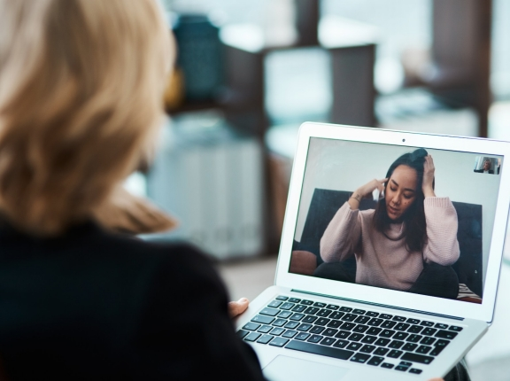 A young woman having a counselling session with a psychologist using a video conferencing tool, photo by PeopleImages/Getty Images