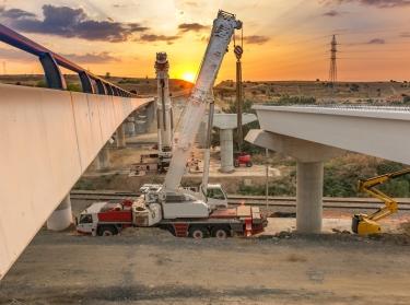 Crane trucks in the construction of a bridge, photo by Juan Enrique del Barrio/Adobe Stock