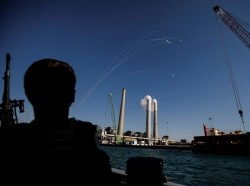An Israeli soldier watches as Israel's Iron Dome anti-missile system intercept rockets launched from the Gaza Strip towards Israel, off the southern Israeli coast, May 19, 2021, photo by Amir Cohen/Reuters