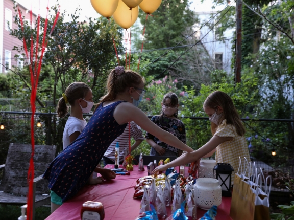 Lydia Hassebroek hands out candy to classmates at her birthday party in Brooklyn, New York, July 12, 2020, photo by Caitlin Ochs/Reuters
