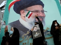 A supporter of Ebrahim Raisi displays his portrait during a celebratory rally for his presidential election victory in Tehran, Iran, June 19, 2021, photo by Majid Asgaripour/WANA (West Asia News Agency) via Reuters