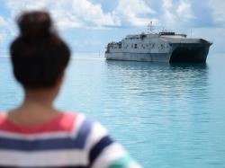 An I-Kiribati girl watches as the Military Sealift Command joint high-speed vessel USNS Millinocket arrives in Tarawa, Republic of Kiribati, June 2, 2015, photo by Chief Petty Officer Jonathan Kulp/U.S. Navy