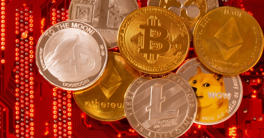 Representations of cryptocurrencies Bitcoin, Ethereum, DogeCoin, Ripple, and Litecoin placed on a PC motherboard, June 29, 2021, photo by Dado Ruvic/Reuters