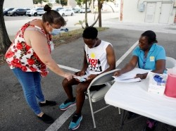 Dieumeeci Ufitimana, (C) signs up to receive the COVID-19 vaccine at Bethel AME Church in St. Petersburg, Florida, July 23, 2021, photo by Octavio Jones/Reuters