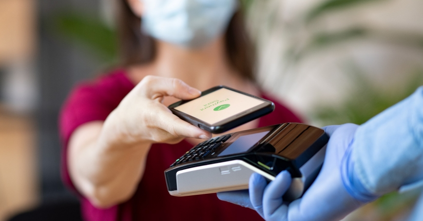 Close up hand of patient paying with smartphone, photo by Ridofranz/Getty Images