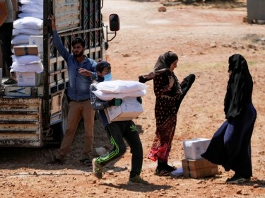 A worker holds bags and a box of humanitarian aid in the opposition-held Idlib, Syria, June 9, 2021, photo by Khalil Ashawi/Reuters