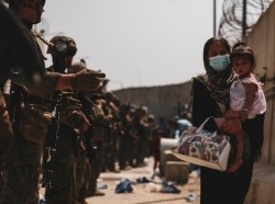 Marines guide a woman and her child during an evacuation from Hamid Karzai International Airport, Kabul, Afghanistan, Aug. 18, 2021, photo by Marine Corps Sgt. Isaiah Campbell/U.S. Department of Defense