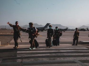 A U.S. Marine escorts Department of State personnel to be processed for evacuation at Hamid Karzai International Airport, Kabul, Afghanistan, August 15, 2021, photo by Sgt. Isaiah Campbell/U.S. Marines via Reuters