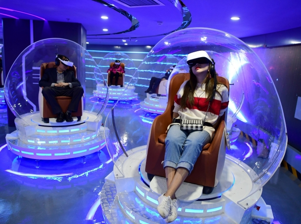 People wearing virtual reality headsets watch films at a newly opened VR cinema by Er Dong Pictures in Beijing, China, March 27, 2019, photo by Lin Hui/Beijing Youth Daily/Reuters