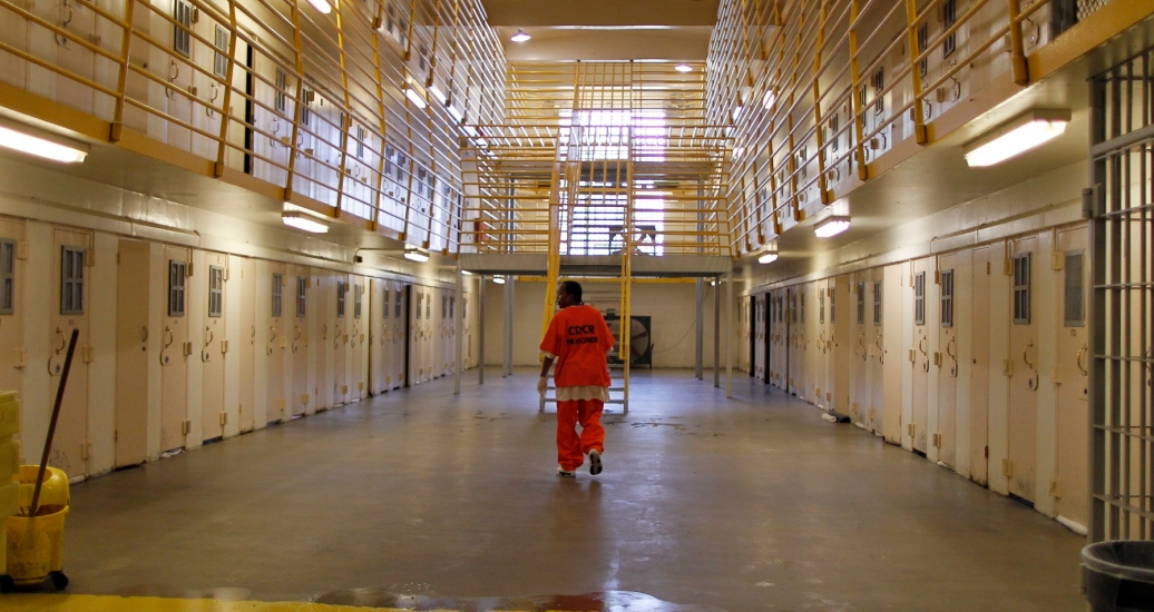 An inmate walks back to his cell after mopping the floor at the California Institution for Men state prison in Chino, June 3, 2011