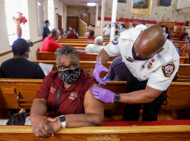 A woman receives a COVID-19 vaccine from a paramedic at the historic Greater Bethel Missionary Baptist Church in Tampa, Florida, February 14, 2021, photo by Octavio Jones/Reuters