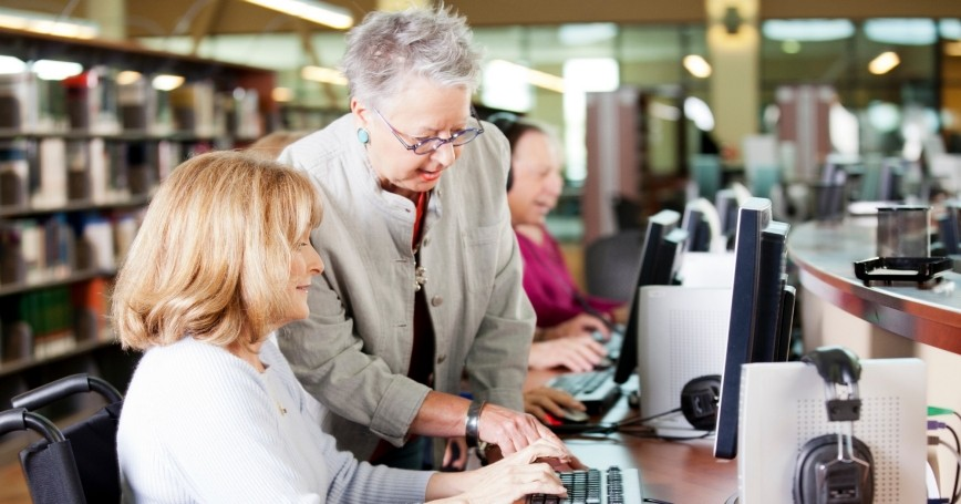 Senior librarian helping people with computers in a library, photo by Alina555/Getty Images