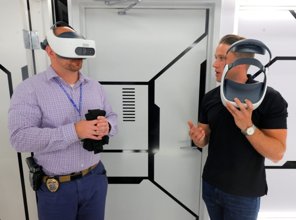 Wayne County Airport Police commander Bryan Birch (L) tries out VR goggles during community engagement training in Taylor, Michigan, August 26, 2021, photo by Eric Seals/Reuters