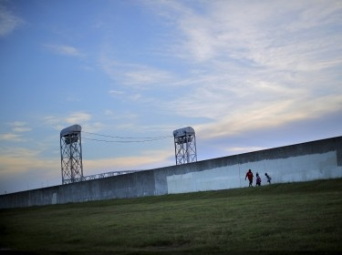 Lower Ninth Ward area residents walk by the reconstructed wall of a levee at the Lower Ninth Ward canal in New Orleans, Louisiana, August 16, 2015, photo by Carlos Barria/Reuters