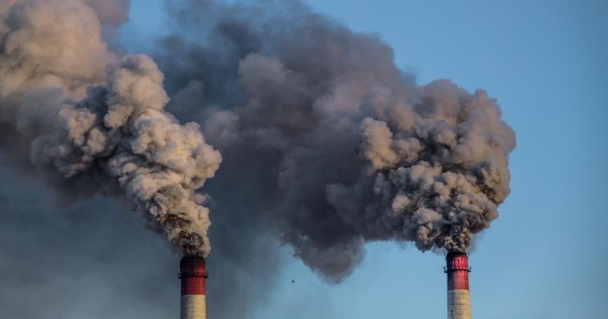 Two industrial chimneys release heavy smoke into the blue sky, photo by kapichka/Adobe Stock