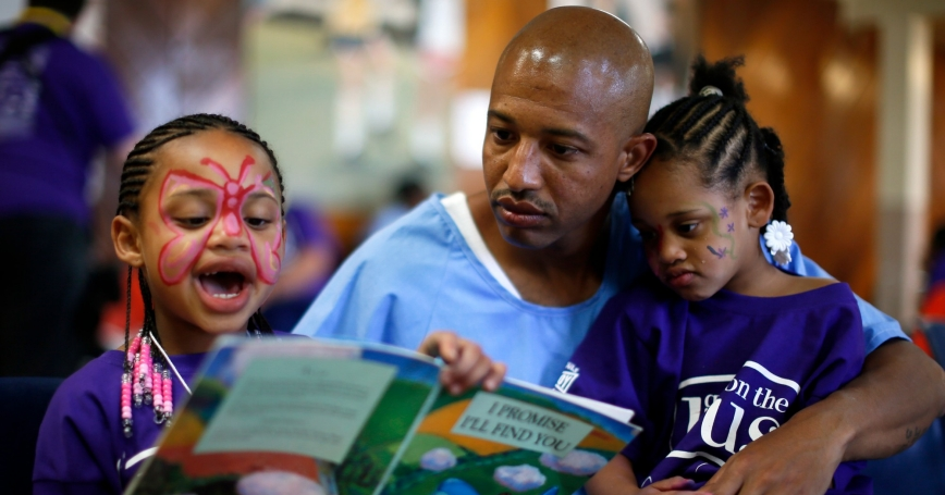 Donte, 34, reads a book with his two daughters during a visit at San Quentin State Prison, June 8, 2012, photo by Lucy Nicholson/Reuters