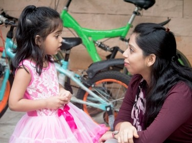 Mother talking to her young daughter with bikes in the background, photo by Dishant_S/Getty Images