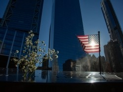 A U.S. flag and flowers on the 9/11 memorial in New York City, New York, January 25, 2020, photo by Nicolas Economou/Reuters