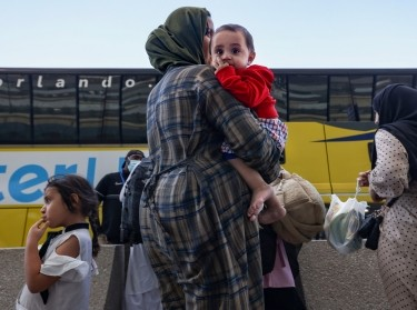 Afghan refugees board buses that will take them to a processing center after arriving at Dulles International Airport in Dulles, Virginia, September 2, 2021, photo by Evelyn Hockstein/Reuters
