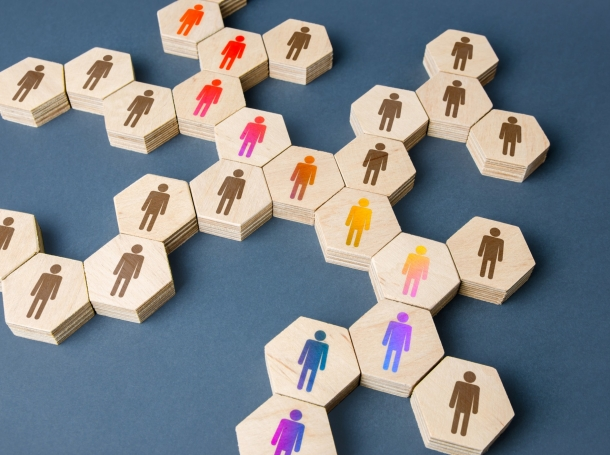 Hexagonal tiles with human figures in different colors representing a chain of communicating people, photo by Andrii Yalanskyi/Getty Images