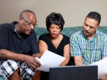 Black family with older parents looking at financial records, photo by Alina555/Getty Images