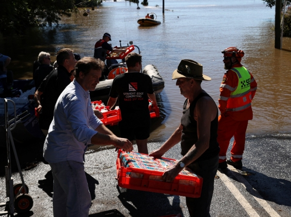 People load a State Emergency Service boat with food for a community stranded after severe flooding, in western Sydney, Australia, March 24, 2021, photo by Loren Elliott/Reuters
