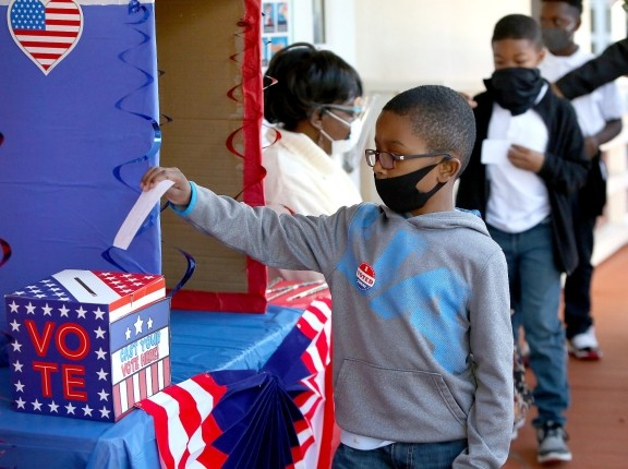 A second grade student votes during a mock election at his school in Gainesville Florida, Nov. 3, 2020, photo by Brad McClenny/Reuters