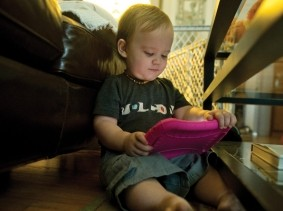 A toddler holds an electronic tablet
