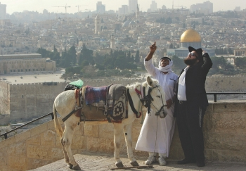 A Palestinian who offers donkey rides to tourists shares a laugh with an Ultra-orthodox Jewish man at the Mount of Olives