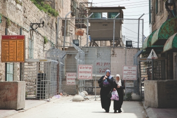 Palestinian women passing an Israeli checkpoint in Al-Shuhada Street in Hebron in the West Bank