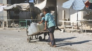 Children carry water next to destroyed shops in the Damascus countryside, in June 2015