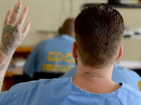 A student raises his hand during a class at the California Institution for Men in Chino, California
