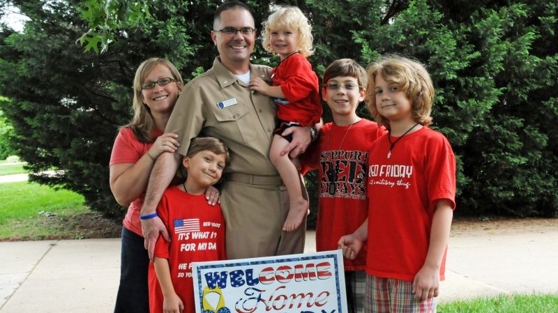 Erin Henderschedt (left) poses with her four sons and husband, Tom, while he was home on leave in 2011