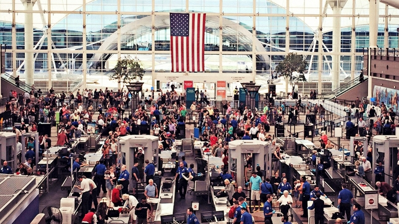 Travelers go through airport security at Denver International Airport in Colorado
