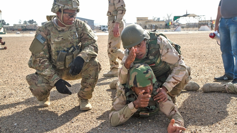 Iraqi Army and U.S. Army soldiers collaborate during a simulation at Camp Taji, Iraq, March 3, 2015